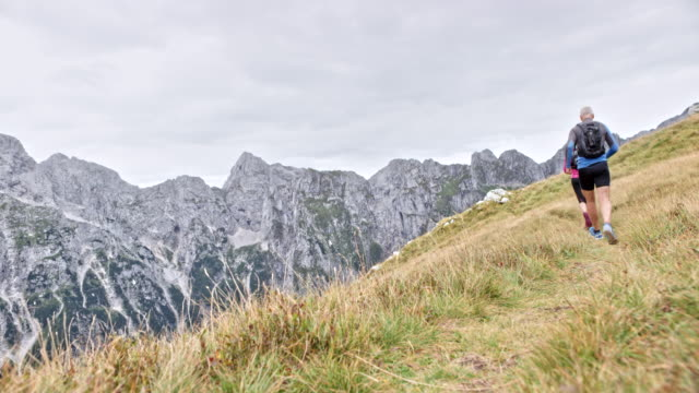 Couple running on a grassy ridge high in the mountains