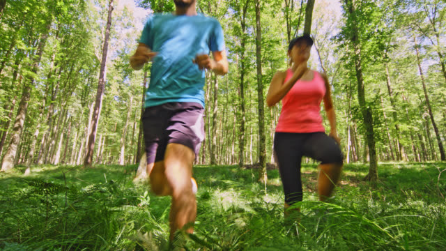 SLO MO Couple running through the forest covered with fern