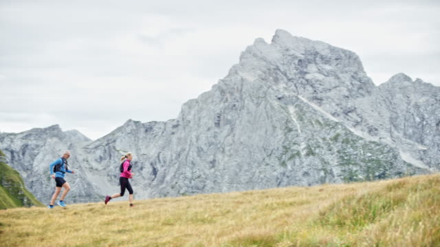 DS Couple running up a grassy mountain ridge high in the mountains