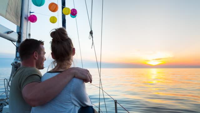 MS couple sailing in mediterranean sea on wooden yacht at sunset
