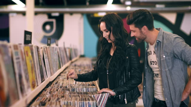 A couple searches through bins of records while shopping.