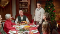 Couple sharing happy news at Christmas table with family
