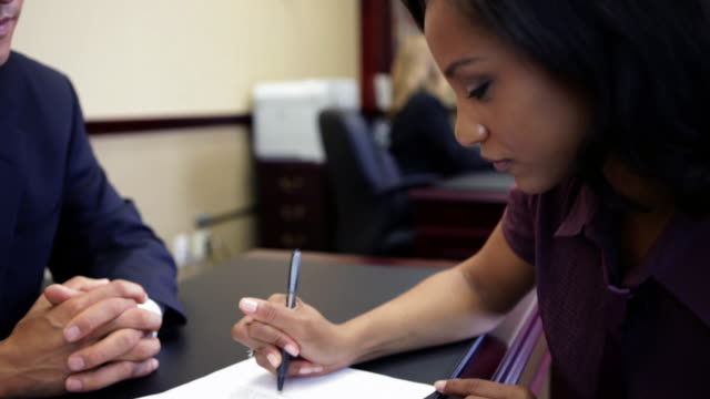 Couple signing paperwork with bank manager in bank