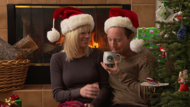 Couple sips hot chocolate by the fireplace and Christmas tree / Bellevue, Idaho, United States