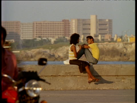 Couple sit on sea wall chatting as traffic passes Havana; 1970's