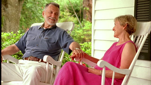 A couple sits in rocking chairs on their front porch.