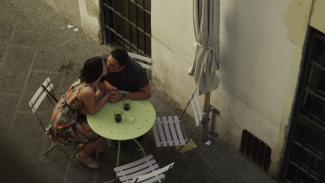 WS HA Couple sitting and kissing at outdoor table / Florence,Tuscany