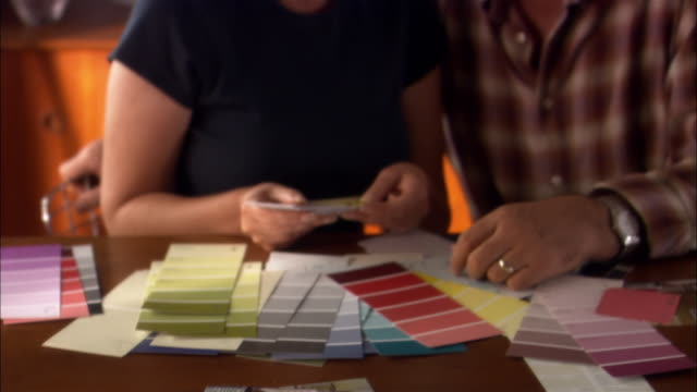 Couple sitting at table comparing paint swatches
