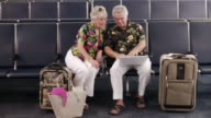 WS Couple sitting in airport departure lounge using laptop / Jacksonville, Florida, USA