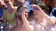 MS Couple sitting in crowd taking self portrait with smart phone during sporting event