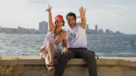 WS SLO MO Couple sitting on cement hedge, Cuban flag waves in foreground / Havana, Cuba