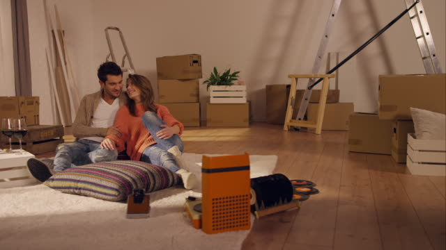 Couple sitting on floor in new apartment