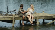 WS of couple sitting on jetty splashing feet in water