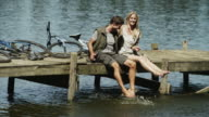 WS of couple sitting on jetty splashing feet in water