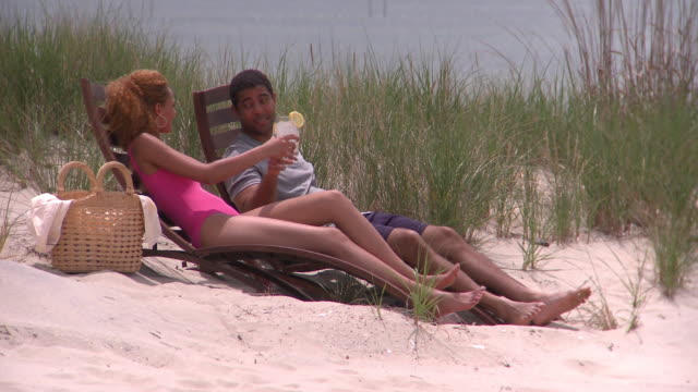 MS Couple sitting on lounge chairs on beach toasting with drinks, Eastville, Virginia, USA