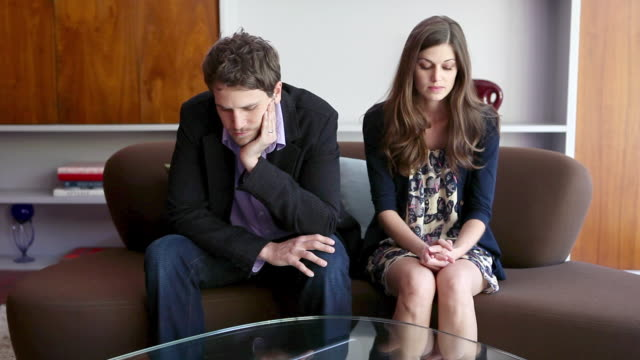 Couple sitting on sofa arguing