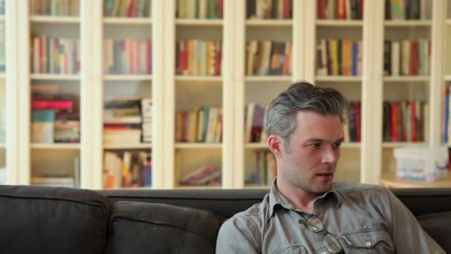 MS Couple sitting on sofa in front of book shelves, looking at laptop / Brooklyn, New York City, USA