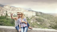 MS PAN Couple sitting on wall on holiday in Alpes Cote d'Azur region taking photos of themselves / Tourrettes Sur Loup, Provence, France