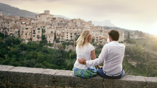 MS Couple sitting on wall on holiday in Alpes Cote d'Azur region with chatting and looking at view of town / Tourrettes Sur Loup, Provence, France+F9