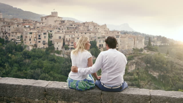 MS PAN Couple sitting on wall on holiday in Alpes Cote d'Azur region with chatting and looking at view of town / Tourrettes Sur Loup, Provence, France