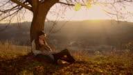 Paar sitzen unter dem Baum bei Sonnenuntergang