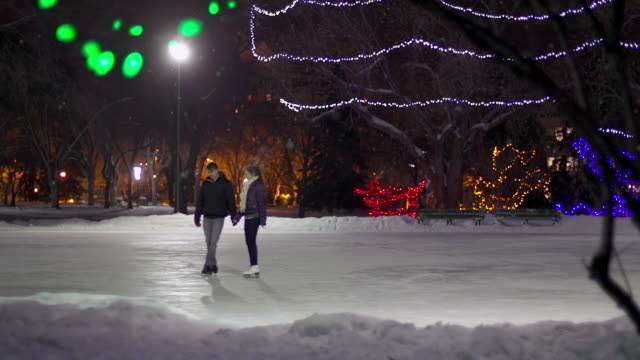 Couple skates together on a snowy winter evening.