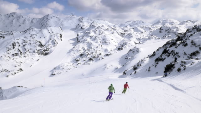 AERIAL Couple skiing down the slope on sunny day