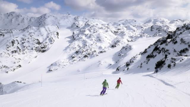 AERIAL paar Skifahren auf der Piste an einem sonnigen Tag