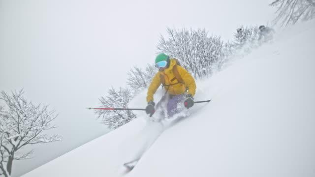 SLO MO Couple skiing in powder snow splashing camera lens