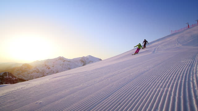 SLO MO Couple skiing on fresh track at sunrise