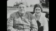 Fatty Arbuckle and Miss Cutie Cuticle (Alice Lake) smile as they ride in a horse carriage