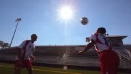 Two soccer players practice head-butting a ball back and forth.