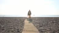 Couple stroll along boardwalk across across empty beach, from sea
