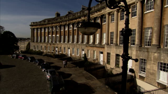 A couple strolls along the curved Royal Crescent in Bath England. Available in HD.