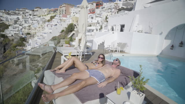 couple sunbathing at poolside in greece