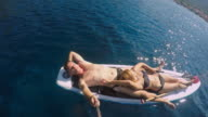 WS Couple sunbathing on a SUP board