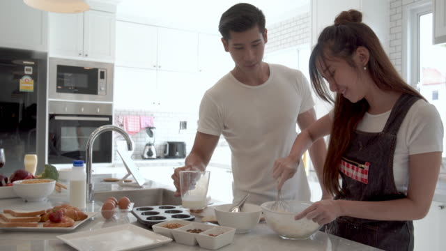 Couple sweet mixing the dough together at home.