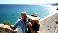 Couple take selfie pic on stone wall above beach