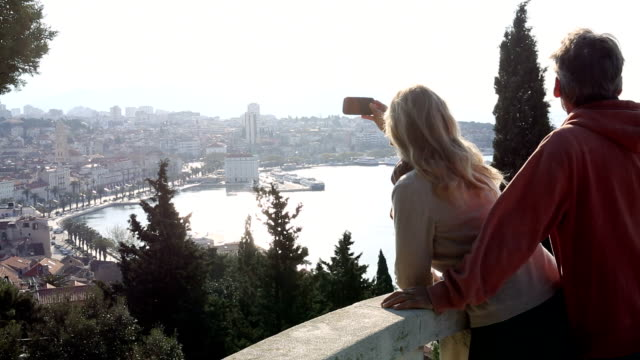 Couple take smart phone pic from viewing platform, above city