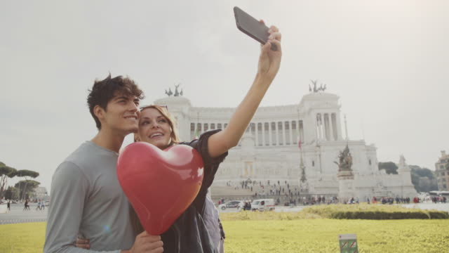 Couple taking a selfie video in Rome with heart