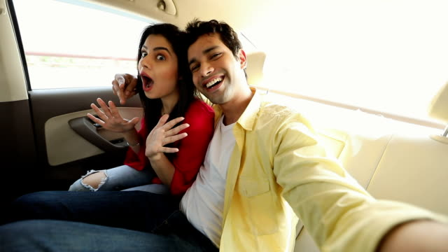 Couple taking selfie with a mobile phone in the car, Delhi, India