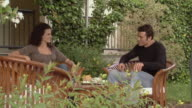 MS Couple talking and drinking afternoon tea in garden / Norcia, Italy