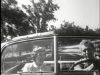 POV, CU, HA, B/W, Couple talking and laughing while driving in convertible car, USA