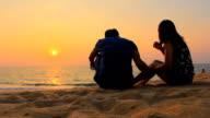 Couple talking at sunset beach