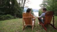 Couple talking in lawn chairs in backyard