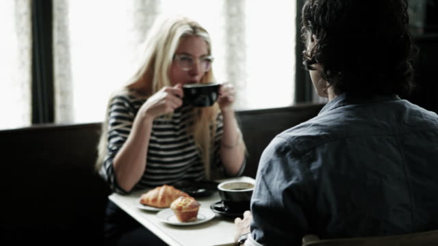 Couple talking over coffee in cafe