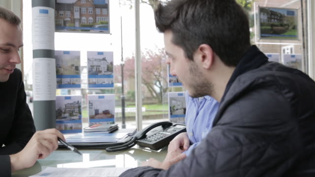 TS A couple talking to an estate agent in his office