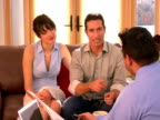 MS, Couple talking to financial advisor in living room