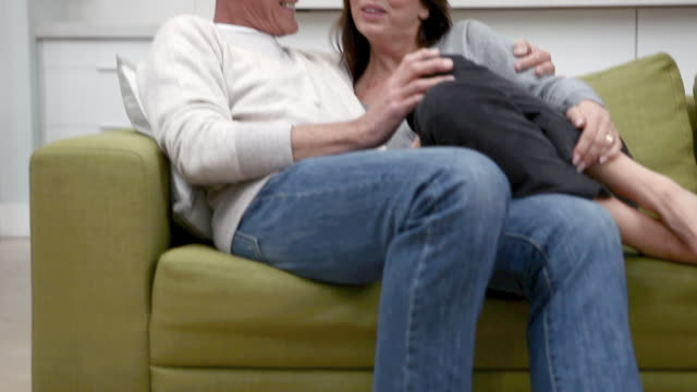 Couple talking together on sofa