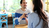 Couple Talking While Sitting At Table In Cafe